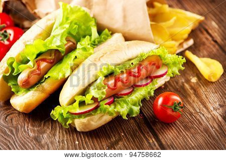 Hot dog. Grilled hot dogs with mustard and ketchup on a picnic wooden table. Sandwich, Hotdog