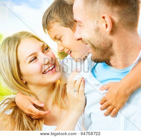 Happy joyful young family father, mother and little son having fun outdoors, playing together in summer park, countryside. Mom, Dad and kid laughing and hugging, enjoying nature outside. Piggyback