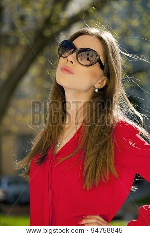Close up portrait of a beautiful young girl in red shirt on the background of the urban landscape