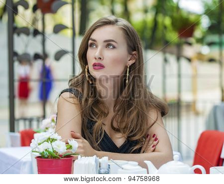 Happy Beautiful young blonde woman sitting in a coffee shop and drink tea