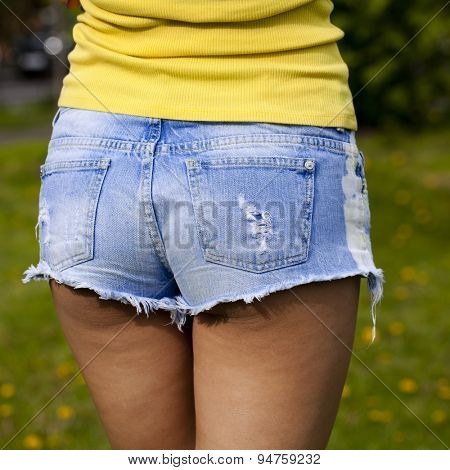 Part of the body, torn blue jeans shorts for women on the background summer street