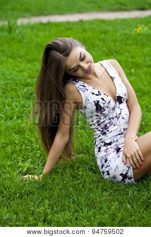 Happy young pretty girl sitting on green grass