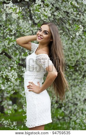 Beautiful young brunette woman in white dress against the background spring flowers trees