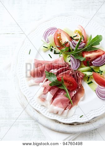 Vegetable salad with serrano ham on a plate