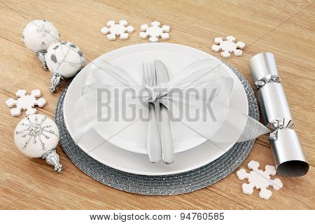 Christmas dinner place setting with plates, cutlery, silver bow, baubles and cracker over light oak background.