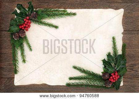 Christmas background floral border with holly, ivy, fir and pine cones on parchment paper over old oak wood.