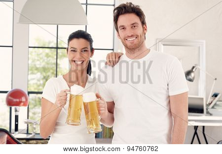 Happy young couple drinking beer at home, clinking glasses, looking at camera.
