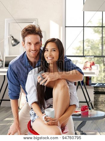 Portrait of happy attractive young loving couple at home, hugging, looking at camera.