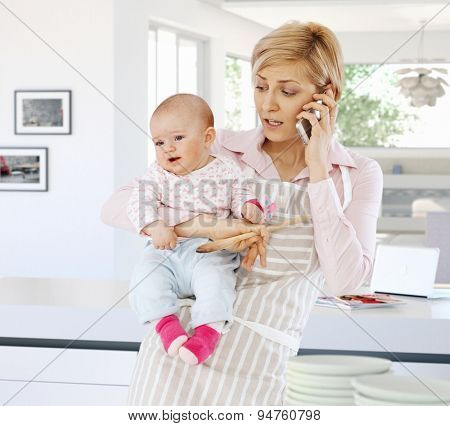 Casual caucasian housewife in kitchen with baby, phone, spoon in hand. Standing, talking on phone. Worried, stressed, busy.