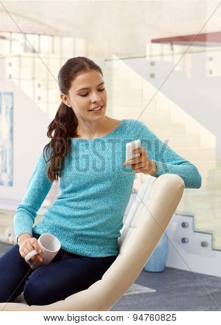 Young casual caucasian brunette girl sitting at home in beige leather chair, mug in hand, using mobile phone, looking at screen. Small smile, calling, indoors,