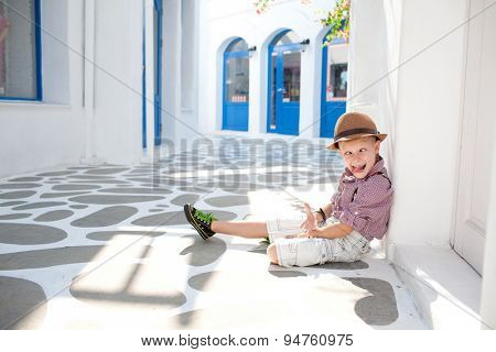 Funny child. Fashionable little boy in sunglasses and hat. Santorini Park