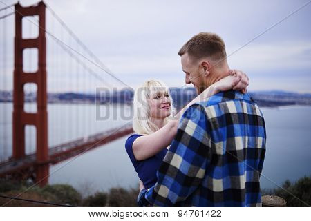 happy romantic couple in front of golden gate bridge on cloudy day