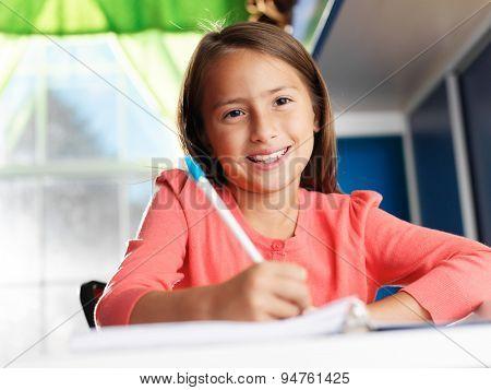 little girl doing home work smiling