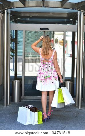 Girl with shopping bags at the hotel's door