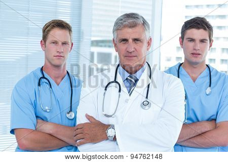 Team of doctors standing arms crossed in the hospital