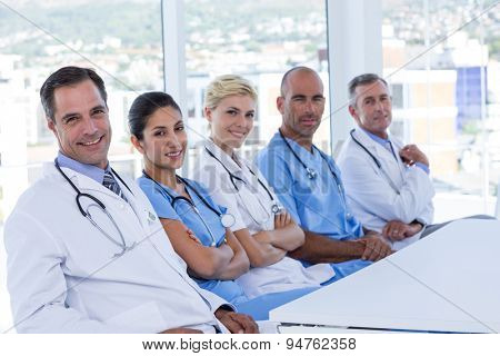 team of doctors looking at camera during meeting in medical office