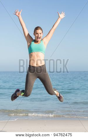 Beautiful fit woman cheering in front of sea at the beach
