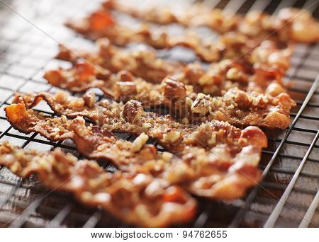 candied bacon with pecans and brown sugar cooling on baking rack