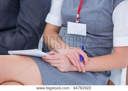 businesswomen taking note during a metting in the office