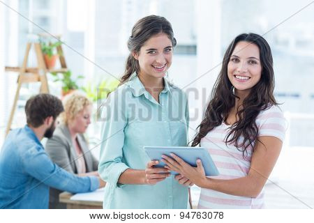 smiling businesswomen using a tablet with colleagues on the office