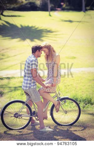 Cute couple on a bike ride in the park on a sunny day