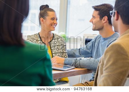 Smiling colleagues talking together in the office