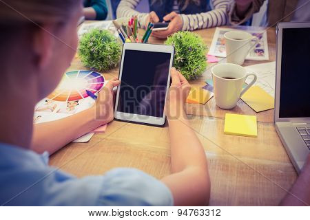 Rear view of casual businesswoman using tablet during a meeting