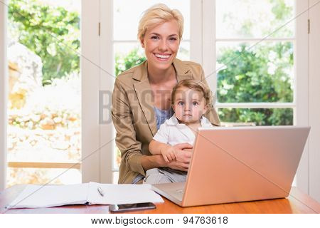 Smiling of pretty blonde woman with his son using laptop in the office