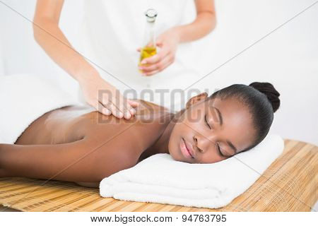 Masseuse pouring massage oil on a pretty woman back at the health spa