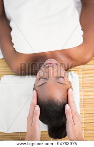 Upward view of a pretty woman enjoying a head massage at the health spa