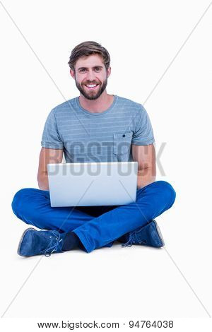 Handsome man looking at camera and using laptop on white background
