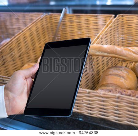 Man using tablet pc against baskets with breads freshly baked and tongs