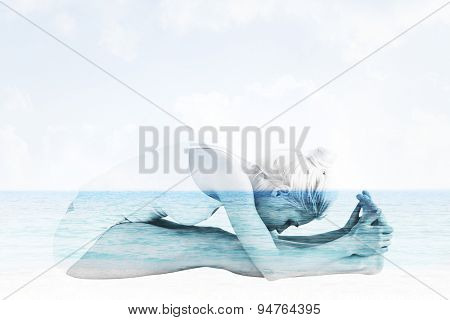 Toned woman doing the paschimottanasana pose against beach scene