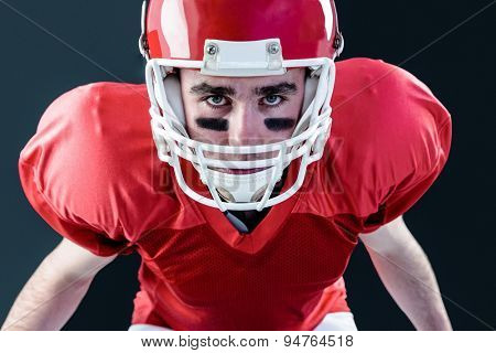 A serious american football player taking his helmet looking at camera with black background