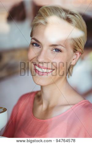 Happy blonde woman smiling at camera and holding a cup of coffee at the coffee shop