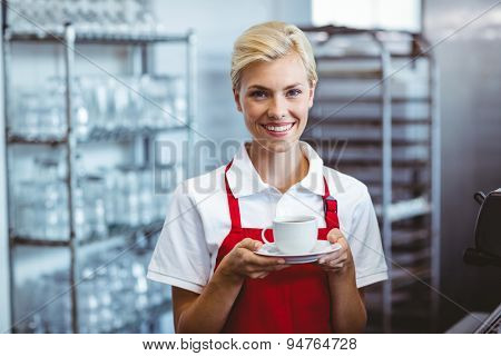 Pretty barista holding a cup of coffee at the cafe
