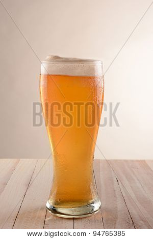 A glass of beer on a rustic wood table with a light to dark gray background.