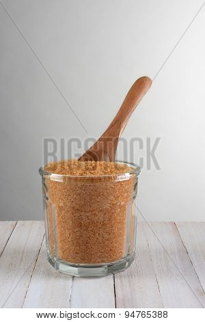 Closeup of a glass sugar bowl full of granulated brown sugar with a wooden spoon. On a rustic wood table against a light to dark gray background. Vertical format with copy space.