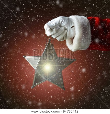 Closeup of Santa Claus holding a star shaped lantern over a red light to dark background with snow. The light from the star is glowing. Only hand and sleeve of Santa are visible.