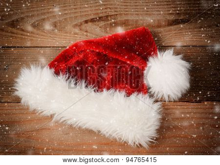 Santa Claus Hat on a rustic wooden floor with snow flakes and an instagram retro look. High angle view with vignette.