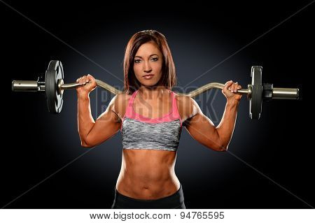 Young woman with weight bar behind neck over dark background