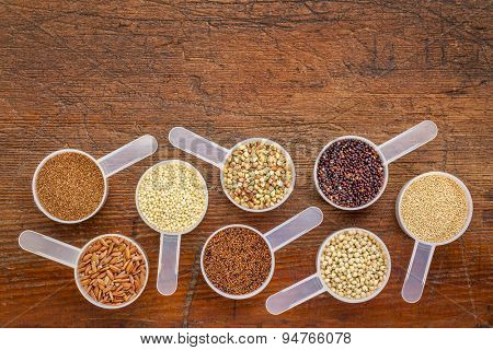gluten free grains (quinoa, brown rice, kaniwa, amaranth, sorghum, millet, buckwheat, teff) - a set of measuring scoops on a rustic wood with a copy space