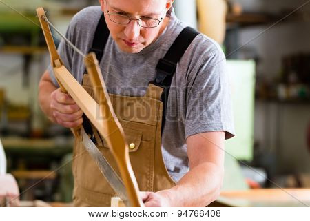 Carpenter working on a hand saw cutting a tenon in drawers in his workshop with bow or frame saw