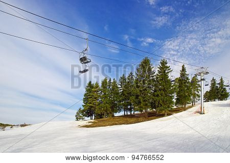 Beautiful winter mountain landscape with ski lift and spruces on slope