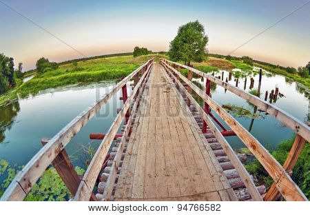 Wooden bridge over the small river. fisheye lens