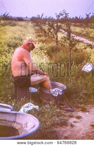 Vintage photo (scanned reversal film) of elderly farmer washing legs outdoor in a basin, early 1970's
