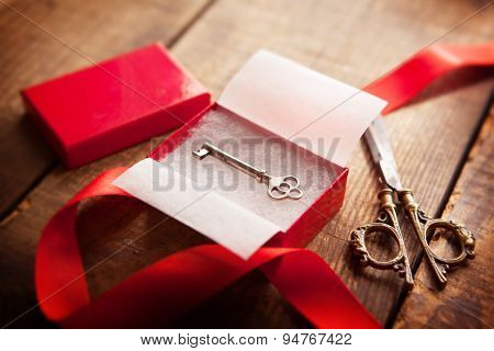 A red gift box with an old, key inside,A red gift box, key,  scissors, and a red ribbon. Focus is on the key.