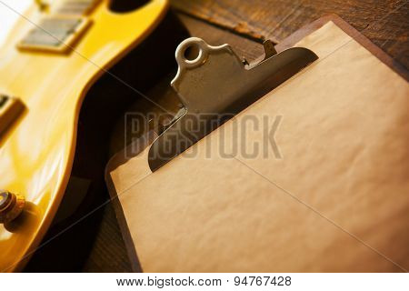 Vintage gold top single cutaway guitar on old wood surface and old clipboard, good for playlists, and production notes. Shallow depth of field.