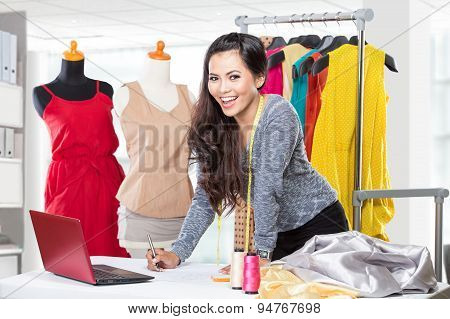 Young Asian Designer Woman Using A Laptop And Smiling,clothes Hanged As Background