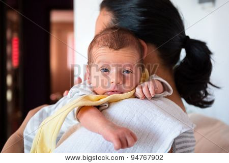 Mother cuddling her baby boy on arm